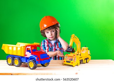 Little curly foreman talking on the phone, playing with trucks and excavators. Close-up. Green background.
