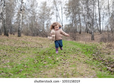 A little curly girl in a brown jacket and pink boots fun runs on the road in the spring forest. Baby running with a Teddy bear with in his hands. Baby slips in wet grass and fall to the ground
