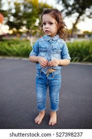 Little curly girl, denim shirt, walking park