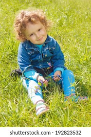 little curly girl sitting on grass in park