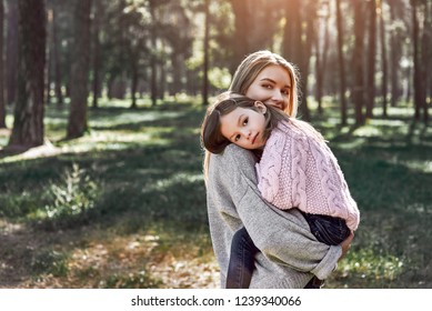A little curly girl in sweater is hugging her mother in woods. Cold season, bright sun is seen through the trees. She is wearing pink sweater and young woman is in grey sweater
