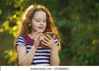Little curly girl using smartphone outdoors. Technology, education concept.