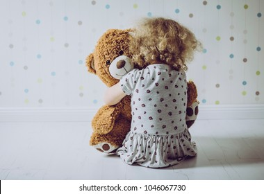 Little curly haired girl crying in her room. Little girl misses it`s mom.