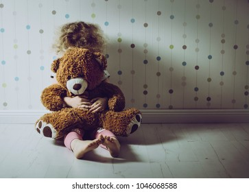 Little curly haired girl crying in her room. Little girl is missing a mom. Hugging stuffed toy teddy bear.