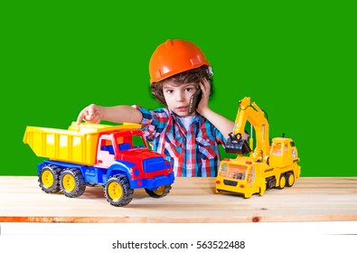 Little curly superintendent sits next to a truck and an excavator, talking on the phone. Close-up. Green background.