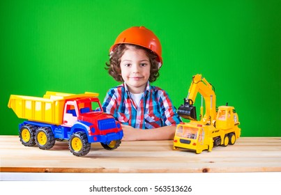 Little curly worker sits surrounded by construction machinery in the construction helmet, looking at the camera. Close-up. Green background.