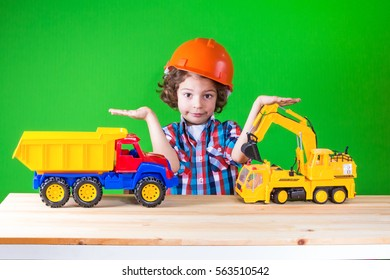 Little curly working in the construction helmet next to the construction machinery, holds imaginary objects. Close-up. Green background.
