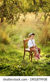 Little curly-haired boy in a cap and pants with suspenders sits on an old chair in an apple orchard