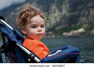 Little curly-haired boy sitting in the pram on the beach and looks into the distance