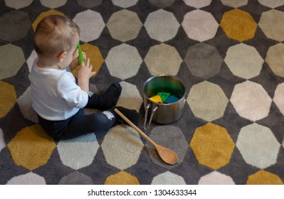 little cute adorable babyboy is sitting on the carpet next to the cooker filled with color forms and the  wood spoon and holding green spoon in hands