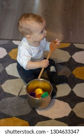 little cute adorable babyboy is sitting on the carpet next to the cooker filled with color forms holding the  wood spoon and looking aside