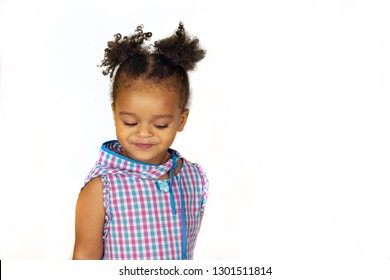Little cute african american baby girl is embarrassed and looks down. Lovely kid wearing bright plaid dress isolated on white background. Copy space in right side