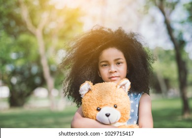 Little cute african american girl hugging embraces an amusing teddy bear against summer nature.