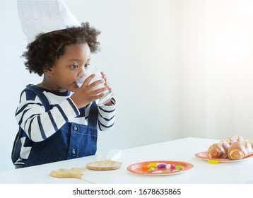 Little cute African kid wearing  a Chef's hat is drinking milk from a glass.Healthy concept.Kid concept.