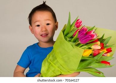 Little cute Asian boy with bouquet colorful tulips