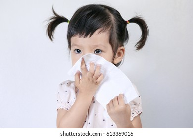 A little cute asian girl blowing his nose with tissue paper in the white background