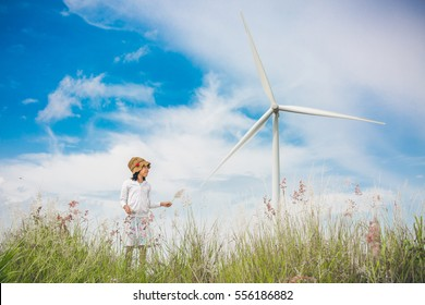 little cute asian girl in looking forward concept at wind power generator turbine in background