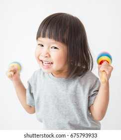 Little cute asian girl playing the maracas isolated on white background, preschool play group