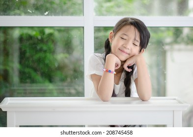Little cute asian girl resting chin by hand