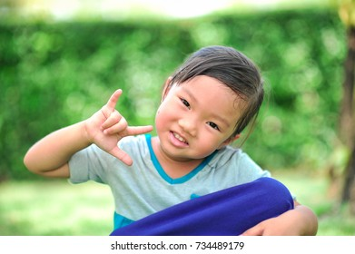 A little cute asian girl show hand in shape of heart and smile on the green grass background. (Selective focus)