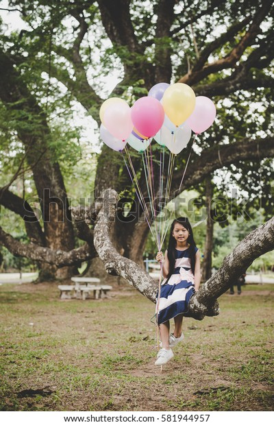 Little cute asian girl sitting on tree branch with colorful of balloons in hand, Relaxing enjoy holiday.