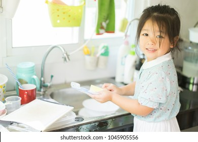 A little cute asian girl washing dishes in kitchen.