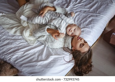 Little cute baby and beautiful mother in bed