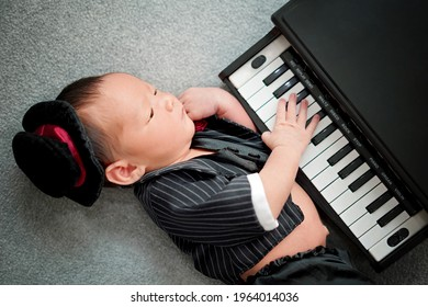 Little cute baby boy playing electronic piano in black tuxedo suit with black hat. lying on grey background.