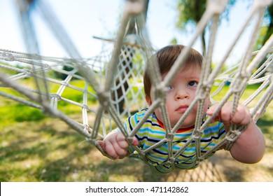 Little cute baby boy relax on a hammock