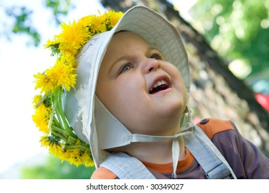 little, cute baby boy wearing a dandelion garland