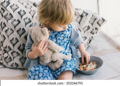Little cute baby girl feeding her teddy bear with almonds nuts.