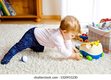 Little cute baby girl learning to crawl. Healthy child crawling in kids room with colorful toys. Back view of baby legs. Cute toddler discovering home and learning different skills