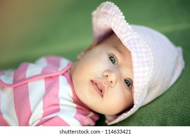 Little cute baby girl in pink on green background looking to camera.
