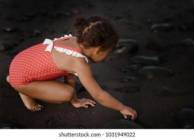 A little cute baby girl is playing on a beach near a sea.