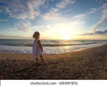 A little cute baby girl is playing on a beach near a sea at sunset. Family, summer vacation concept.