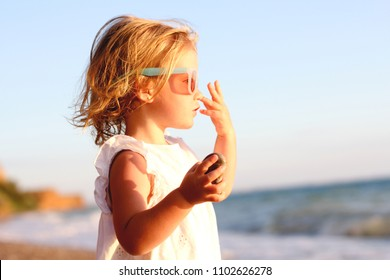 A little cute baby girl is playing on a beach near a sea. Family, summer vacation concept.