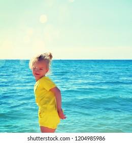 A little cute baby girl is playing on a beach near a sea