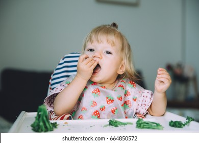 Little cute baby girl sitting in a high white chair and eating broccoli