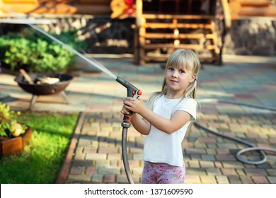 Little cute baby girl watering fresh green grass lawn mear house backyard on bright summer day. Child having fun playing with water hose sprinkler