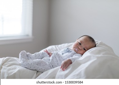 Little cute baby lying with milk bubble on his mouse. Child is 4 months old.