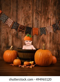 A little cute baby is sitting in a wood basket with Halloween fall pumpkins around the child for a seasonal portrait message