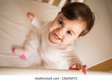 Little cute baby smiling at camera in her cot