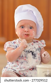 A little cute baby-girl with cooking hoods on her head is sitting on the kitchen floor, chewing on cookies; she is heavily soiled with wheat flour - she's playing cook