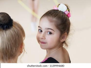Little cute ballerina in studio looking on camera.