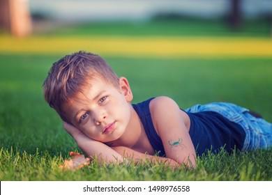 Little cute blond boy lying in the grass