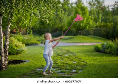 Little cute blond girl with butterfly net in a green garden.