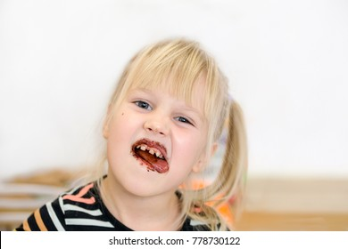 Little cute blond girl with dirty face eating chocolate cake and making grimace showing tongue.