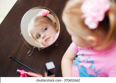 little cute blonde girl smiling three - four years in a pink dress with two tails sits near the mirror with a set of cosmetics and doing makeup, lipstick, cheek colors large fluffy brush for powder