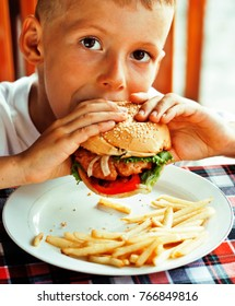 little cute boy 6 years old with hamburger and french fries maki