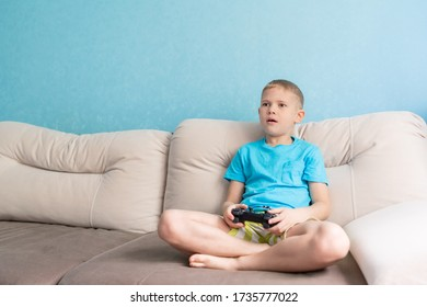 Little cute boy in blue t-shirt play with joystick in electronic game